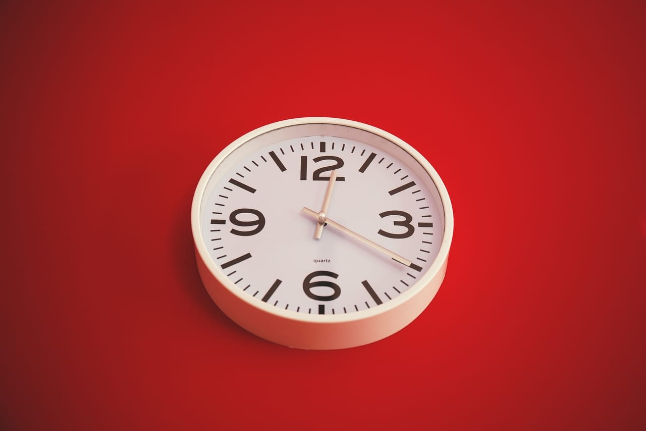 analog-clock-on-red-background